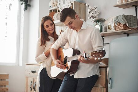 Performance for a woman at the home. Young guitarist playing love song for his girlfriend in the kitchen. Stock Photo