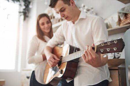 Concentrated husband. Young guitarist playing love song for his girlfriend in the kitchen. Stock Photo