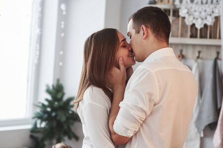 Feeling good. Happy couple kissing in the kitchen. Having nice weekend together. Stock Photo