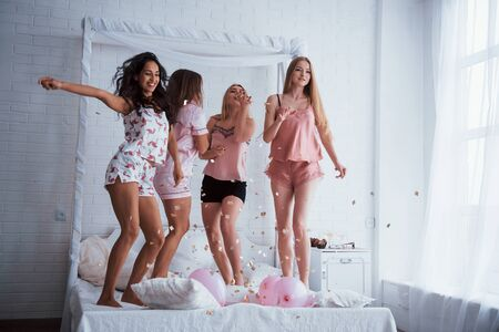 Like kids in the new year. Confetti in the air. Young girls have fun on the white bed in nice room.