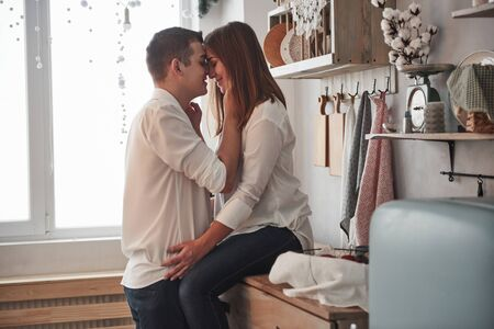 Side view. Happy couple kissing in the kitchen. Having nice weekend together. Stock Photo
