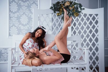 Two girls at the bachelorette party sits and laying on the white bench.