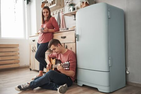 Guy sits on the floor. Young guitarist playing love song for his girlfriend in the kitchen. Stock Photo