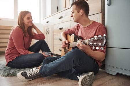 Singing the serenade. Young guitarist playing love song for his girlfriend in the kitchen.