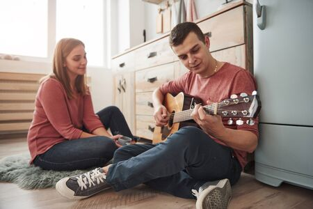 Take a moment to listen to this. Young guitarist playing love song for his girlfriend in the kitchen. Archivio Fotografico