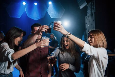 Careful with drinks. Group of young friends smiling and making a toast in the nightclub.