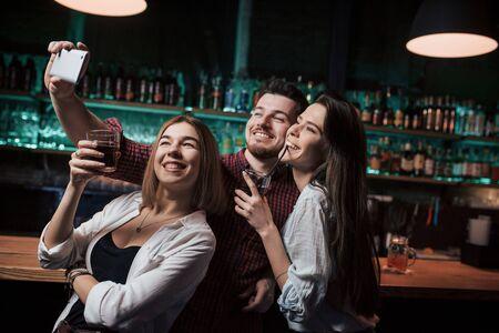 Molte bottiglie con alcol dietro. Amici che prendono selfie in una bellissima discoteca. Con bevande in mano.
