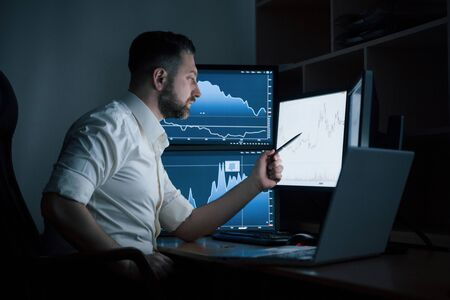 Compares expected results. Bearded man in white shirt works in the office with multiple computer screens in index charts. 版權商用圖片