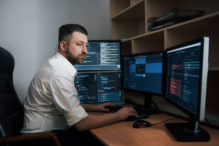Program codes is everywhere. Bearded man in white shirt works in the office with multiple computer screens in index charts. 版權商用圖片