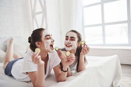 Interesting how its taste. Conception of skin care by using white mask and cucumbers on the face. Two female sisters have weekend at bedroom.