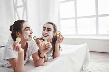 Going to eat that. Conception of skin care by using white mask and cucumbers on the face. Two female sisters have weekend at bedroom. Stock Photo