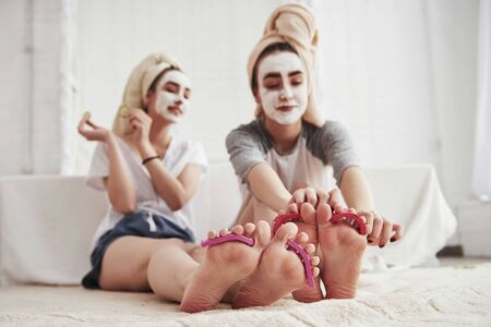 I think its done. Pedicure and painted leg nails. Conception of skin care by using white mask and cucumbers on the face.