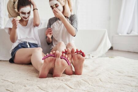 Having conversation. Pedicure and painted leg nails. Conception of skin care by using white mask and cucumbers on the face.
