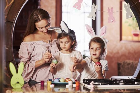 Cute family members. Have happy easter. Two little girls learning how to paint eggs for the holidays. Stock Photo - 134886365