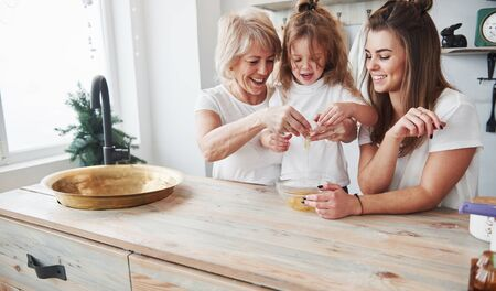 Well done, youre already good at this. Mother, grandmother and daughter having good time in the kitchen.