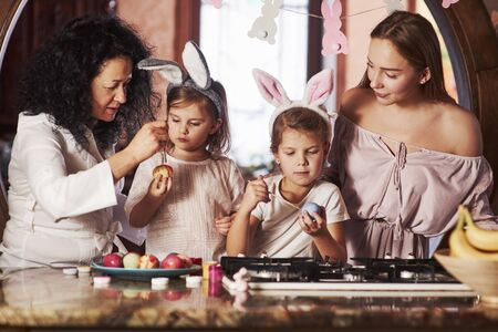Family leisure. Have happy easter. Two little girls learning by parents how to paint eggs at the holidays.
