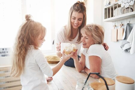Mother, grandmother and daughter having good time in the kitchen.
