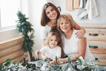 Poartrait near the plants. Mother, grandmother and daughter having good time in the kitchen.