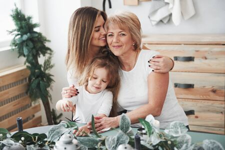 Cute hugs. Mother, grandmother and daughter having good time in the kitchen.