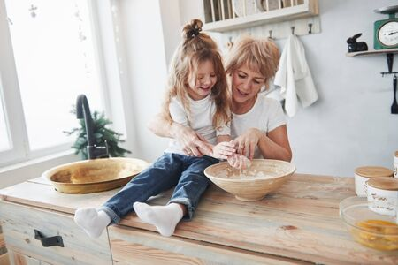 Preparing food goes fun. Grandmother and granddaughter having good time in the kitchen.