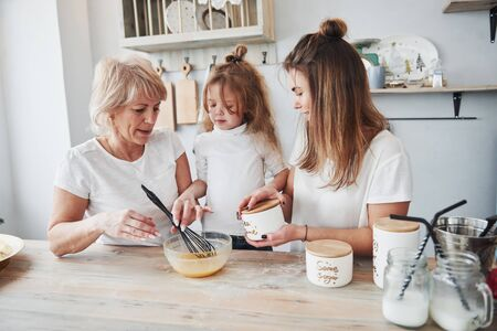 Now lets add some seasoning. Mother, grandmother and daughter having good time in the kitchen. 스톡 콘텐츠
