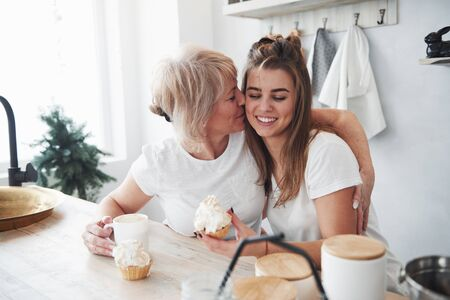 Cute kiss. Mother and daughter having good time in the kitchen.
