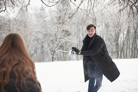 Boyfriend runs forward. Gorgeous young couple playing and throwing snowballs in winter forest.