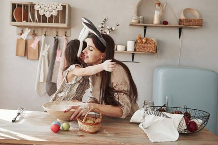 Be careful with the flour. Mother and daughter in bunny ears at easter time have some fun in the kitchen at daytime. 版權商用圖片