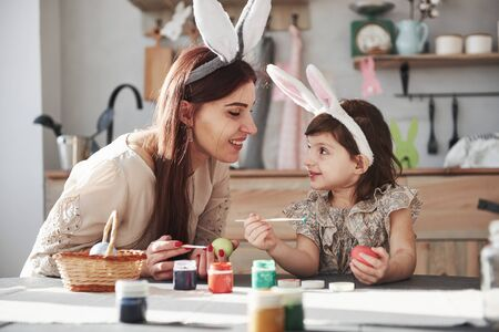 Sitting at the table and painting eggs together. Mother and daughter in bunny ears at easter time have some fun in the kitchen at daytime. Imagens