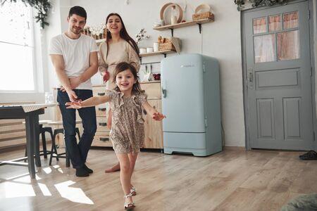 Kijkend naar de dochter. Speels vrouwelijk kind heeft plezier door overdag in de keuken te rennen voor haar moeder en vader. Stockfoto