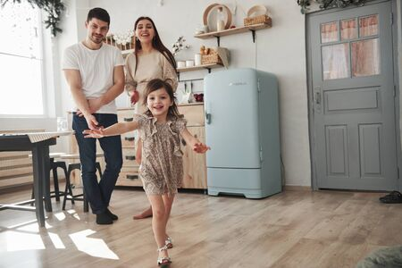 Looking at the daughter. Playful female child have fun by running in the kitchen at daytime of front of her mother and father. Reklamní fotografie