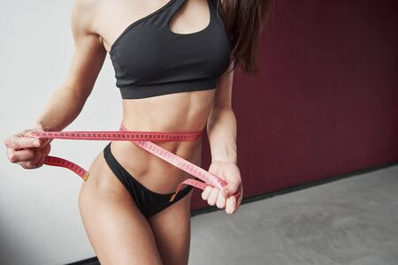 Width of the waist. Close up view of young girls fitness slim body measuring by the tape. Stock fotó
