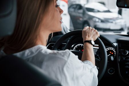 Be careful on the turns. Beautiful blonde girl sitting in the new car with modern black interior.