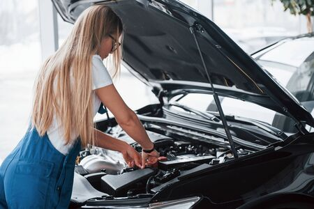 Problem will be solved. On the lovely job. Car addicted woman repairs black automobile indoors.