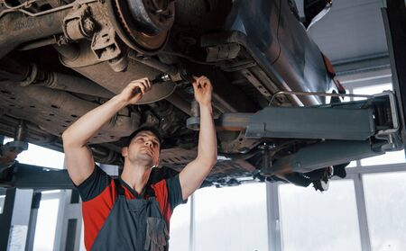 Twists the nuts. Man at the workshop in uniform fixes broken parts of the modern car.