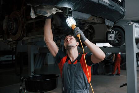 Its dark up there. Man at the workshop in uniform fixes broken parts of the modern car.
