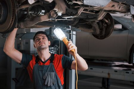 Professional in action. Man at the workshop in uniform fixes broken parts of the modern car. Banco de Imagens