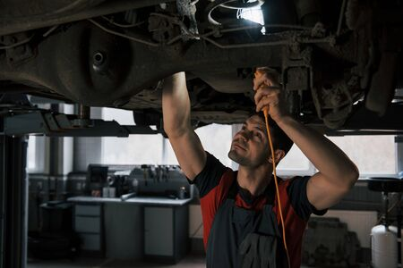 Hard to see some things. Man at the workshop in uniform fixes broken parts of the modern car. Banco de Imagens