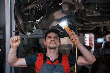 Problem will be solved very soon. Man at the workshop in uniform fixes broken parts of the modern car. Banco de Imagens