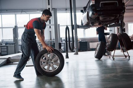 Two people. Mechanic holding a tire at the repair garage. Replacement of winter and summer tires. Imagens