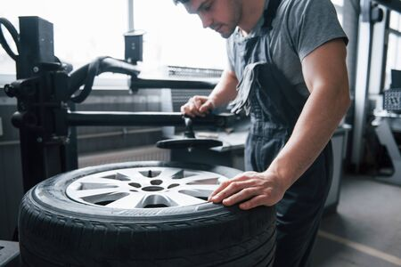 Looks already nice. Young man works with wheels disks at the workshop at daytime.