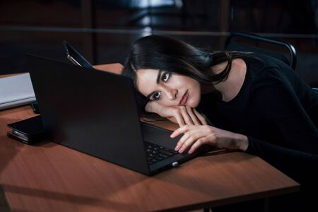 Lying on the table. Attractive brunette businesswoman works alone in the office at nightime. Imagens
