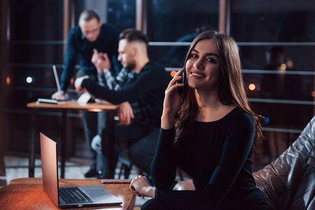 Affascinante donna positiva. Team di giovani uomini d'affari lavora al loro progetto di notte in ufficio. Archivio Fotografico