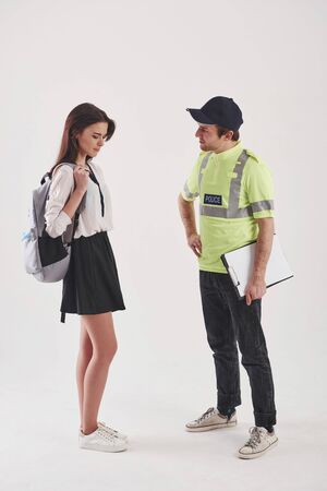 Helping the woman. Policeman in green uniform have conversation with young female student against white background in the studio.