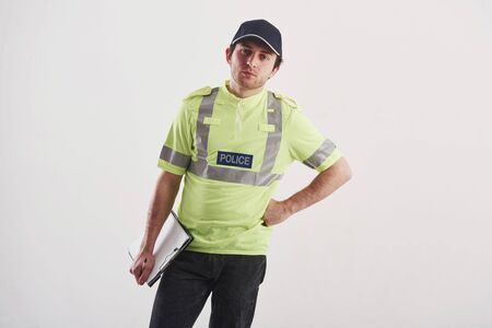 Im listening to you. Policeman in green uniform stands against white background in the studio.
