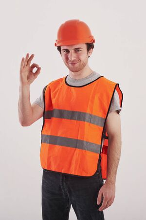 Everything will be okay. Man in orange colored uniform stands against white background in the studio. Banco de Imagens