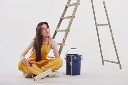 I know what color will be nice for that part of the room. Beautiful brunette in yellow uniform and blue colored bucket sits near the ladder.