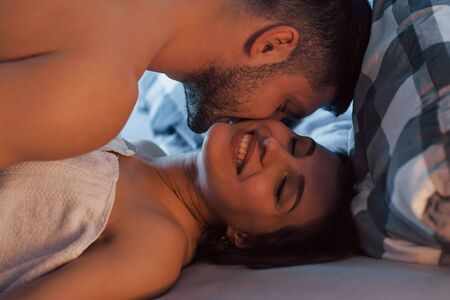 Sirl is smiling, man gives a kiss. Sexy couple lying on the bed and enjoying themselves at morning time.
