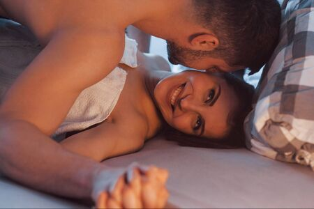 Cheerful woman. Sexy couple lying on the bed and enjoying themselves at morning time.