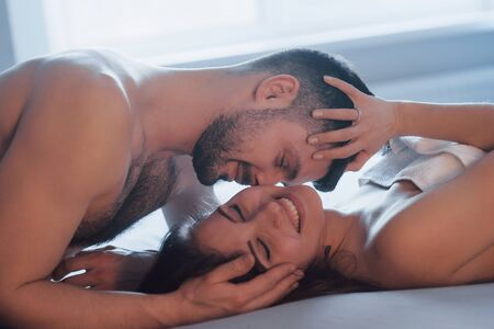 Laughing together. Sexy couple lying on the bed and enjoying themselves at morning time.